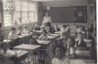 A classroom full of students and a teacher standing at the front