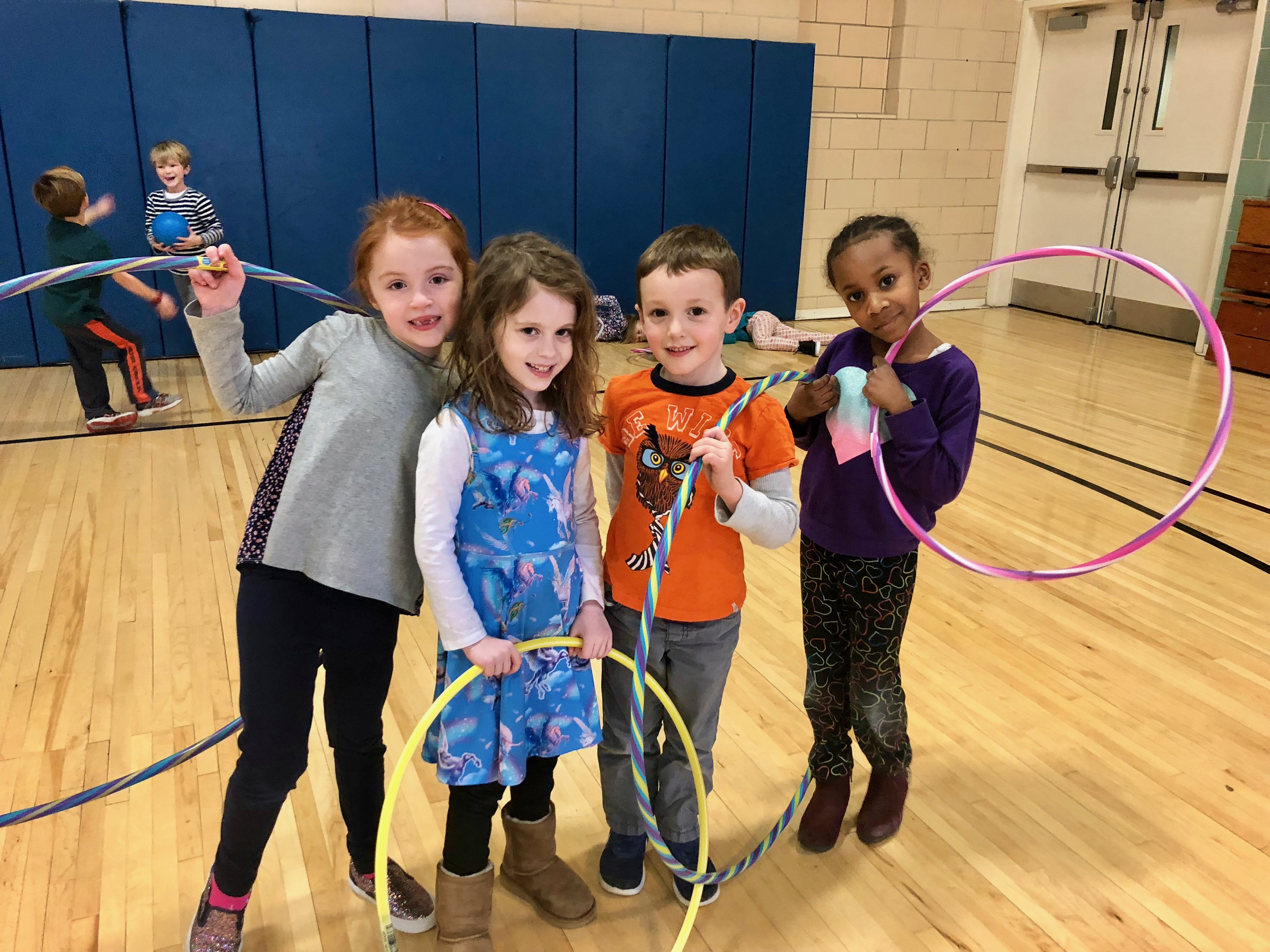 Young children in a gym holding hoola-hoops