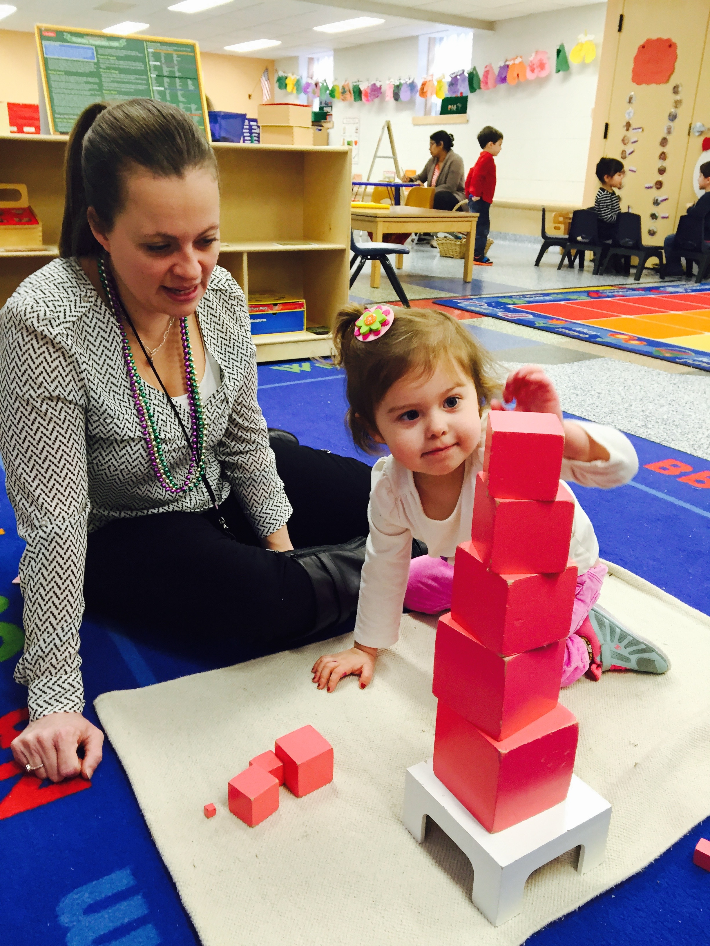 A teacher and young girl playing with blocks in a early childhood classroom