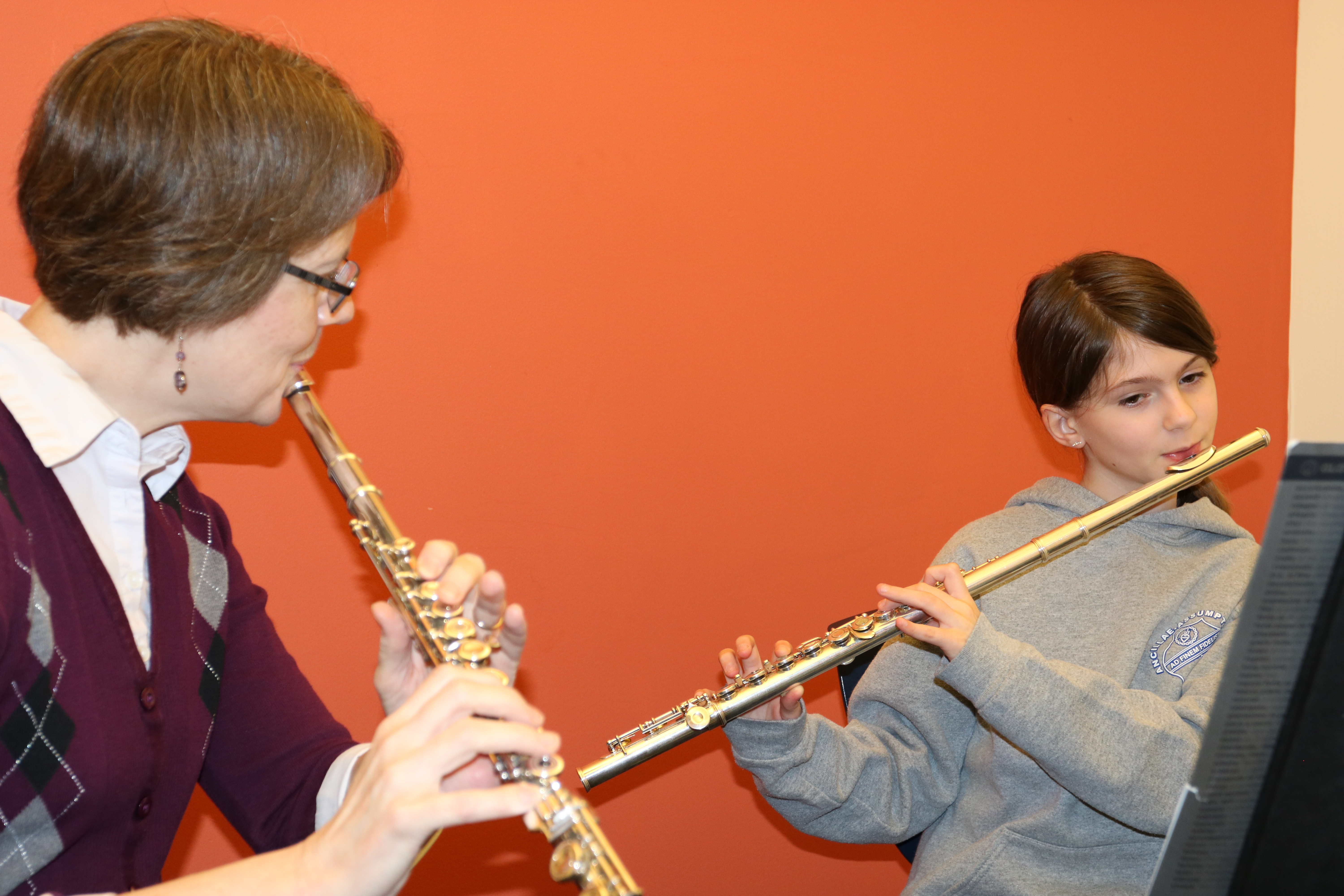 An instructor and a young girl practicing the flute