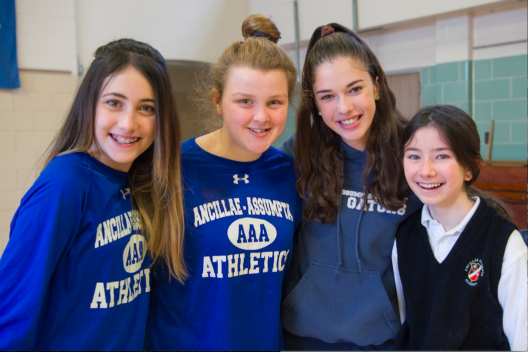 Four girls standing in a gym in Ancillae-Assumpta Academy athletic gear