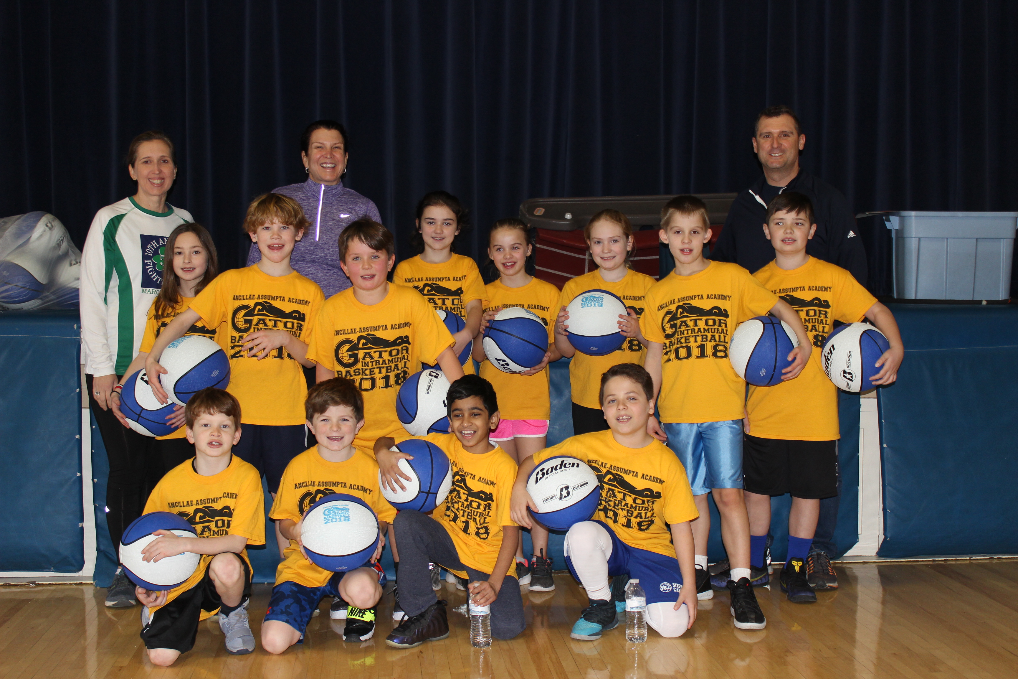 A group of students and teachers in a gym holding basketballs