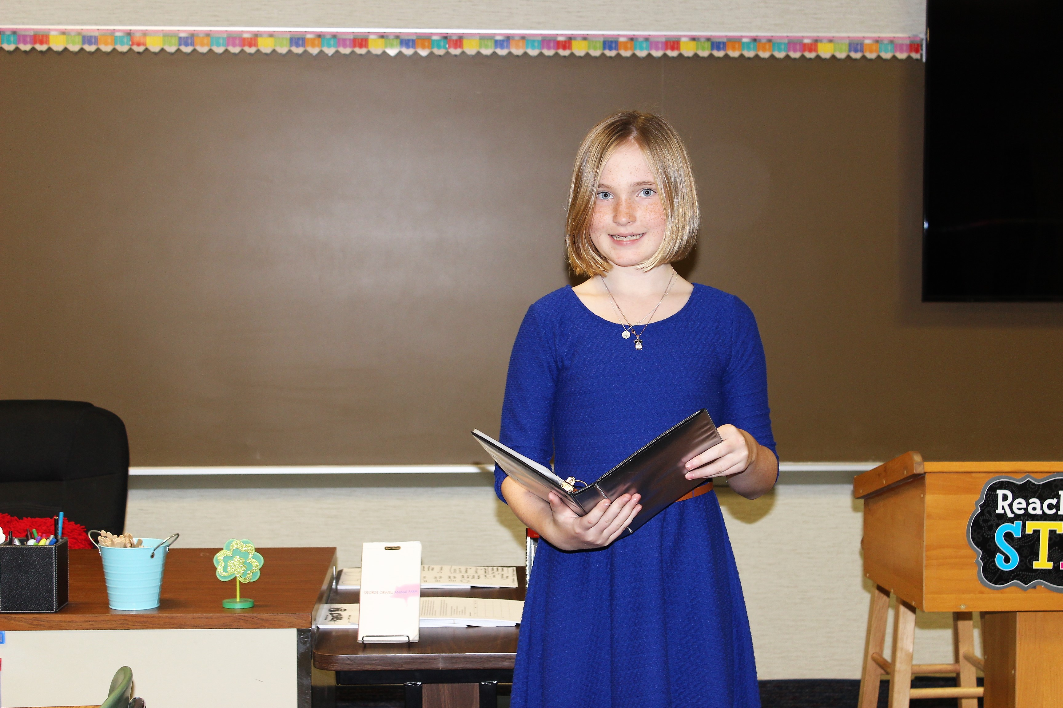 A girl holding a binder standing at the front of a classroom