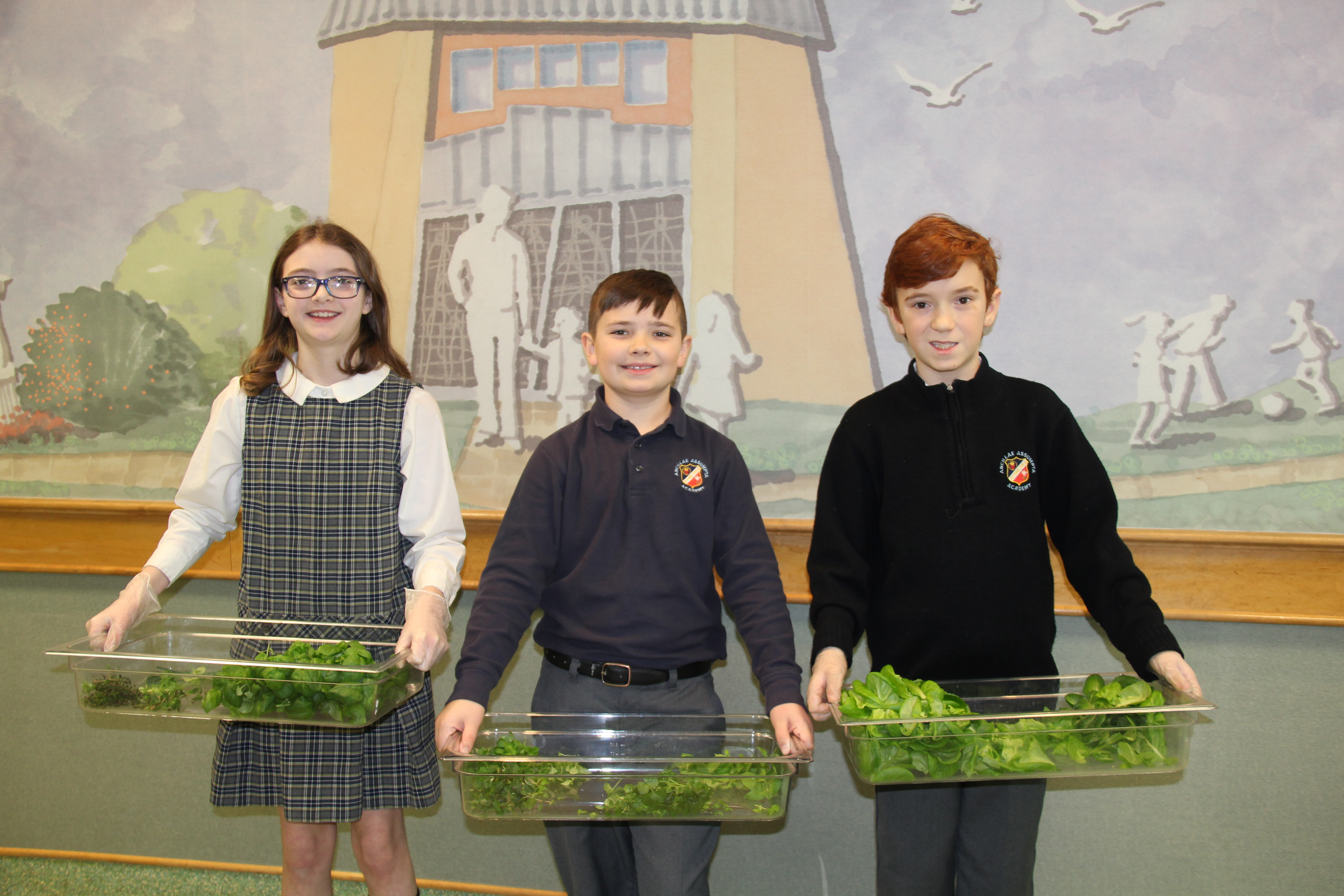 Three students each holding a bin of green produce